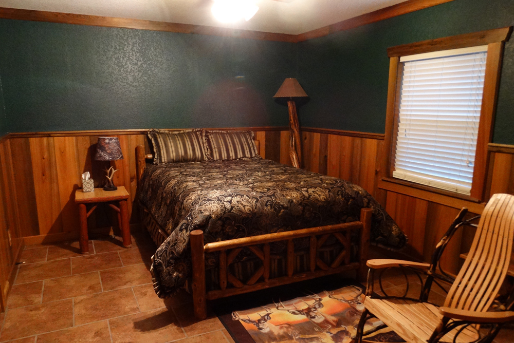 Green bedroom with queen size bed and rocking chair